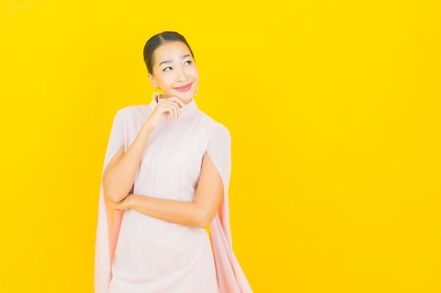 Glimlach van de portret de mooie jonge aziatische vrouw met veel actie op gele muur