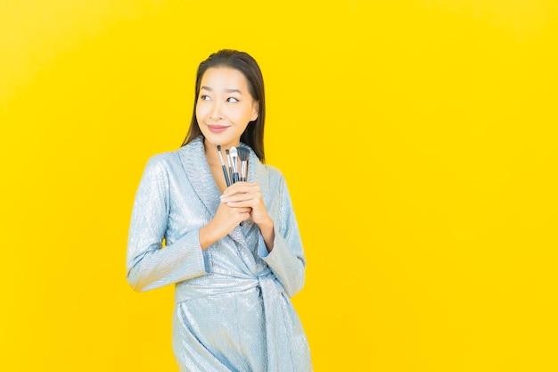Glimlach van de portret maakt de mooie jonge aziatische vrouw met schoonheidsmiddel omhoog borstel op gele muur
