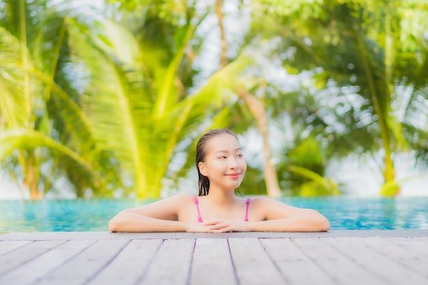 Glimlach van de portret ontspant de mooie jonge aziatische vrouw rond openluchtzwembad in resorthotel op de reis van de vakantiereis