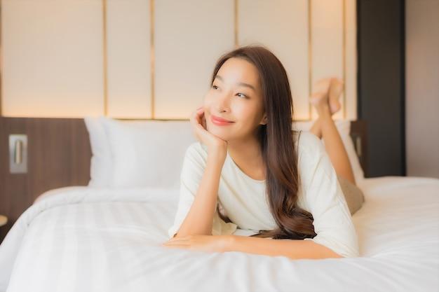 Glimlach van de portret ontspant de mooie jonge aziatische vrouw vrije tijd op bed in slaapkamerbinnenland