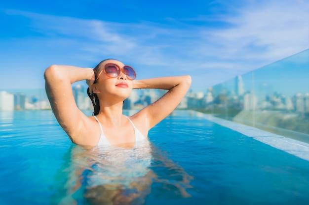 Glimlach van de portret ontspant de mooie jonge aziatische vrouw vrije tijd rond openluchtzwembad met stadsmening
