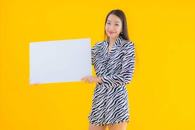 Glimlach van de portret toont de mooie jonge aziatische vrouw met leeg wit aanplakbord op geel