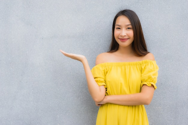Glimlach van portret de mooie aziatische vrouwen gelukkig met concrete achtergrond