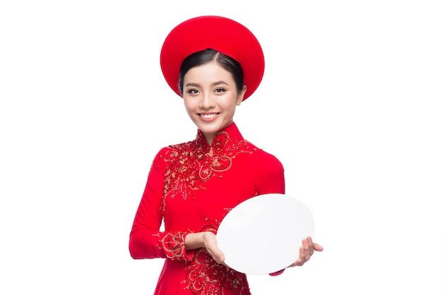Glimlach vietnamese vrouw in jurk traditionele ao dai en introduceren product op witte achtergrond.