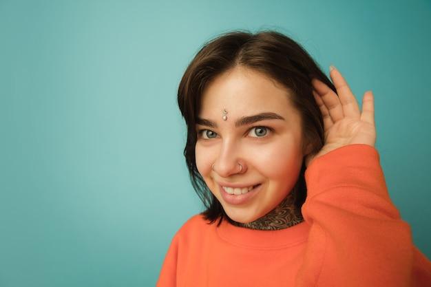Glimlachen, close-up. portret van de blanke vrouw geïsoleerd op blauwe muur met copyspace. mooi vrouwelijk model in oranje hoodie. concept van menselijke emoties, gezichtsuitdrukking