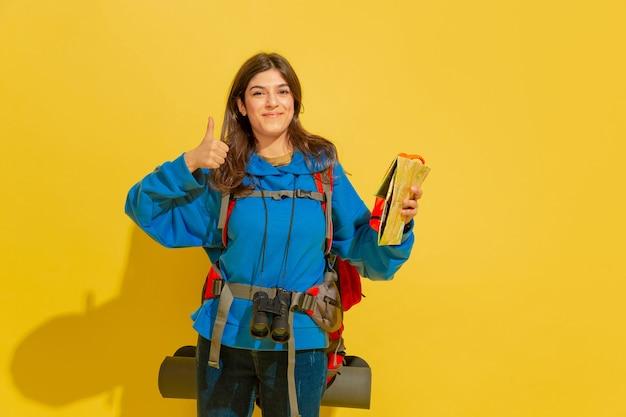 Glimlachen, duimen opdagen. portret van een vrolijk jong kaukasisch toeristenmeisje met zak en verrekijker dat op gele studioachtergrond wordt geïsoleerd. voorbereiden op reizen. resort, menselijke emoties, vakantie.