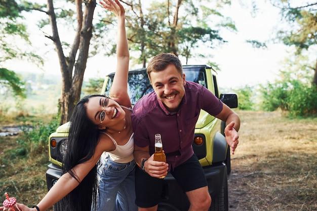 Glimlachen en plezier maken. een paar jonge mensen met alcohol hebben plezier in het bos. groene jeep erachter.