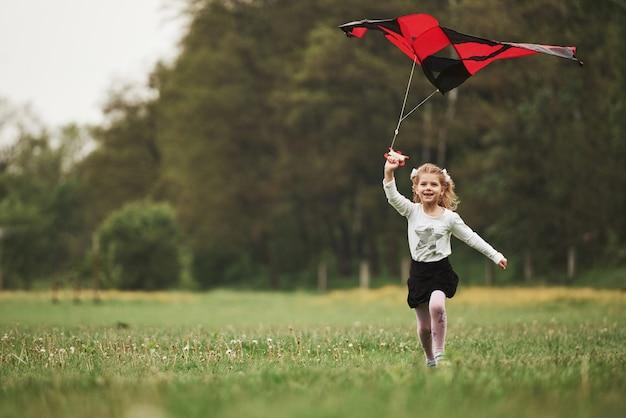 Glimlachen en plezier maken. gelukkig meisje in vrijetijdskleding met vlieger in het veld. prachtige natuur