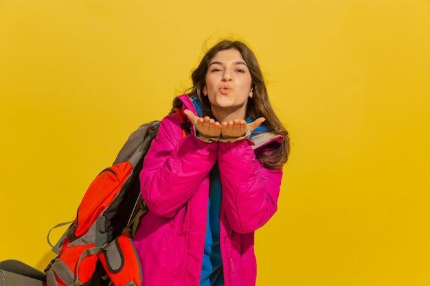Glimlachen, kus verzenden. portret van een vrolijk jong kaukasisch toeristenmeisje met zak en verrekijker dat op gele studioachtergrond wordt geïsoleerd.