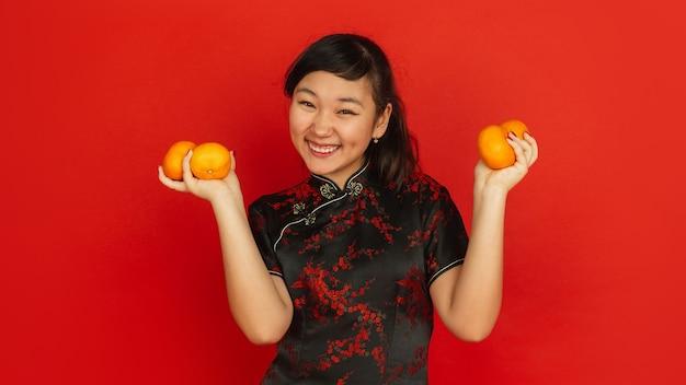 Glimlachen, mandarijnen geven. gelukkig chinees nieuwjaar 2020. portret van aziatisch jong meisje op rode achtergrond. vrouwelijk model in traditionele kleding ziet er gelukkig uit. viering, emoties. copyspace.