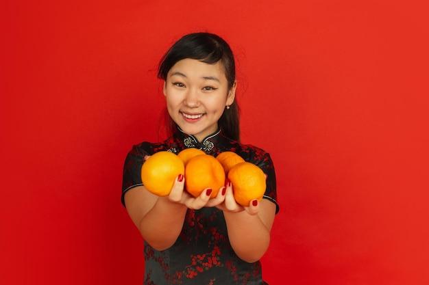 Glimlachen, mandarijnen geven. gelukkig chinees nieuwjaar. aziatisch jong meisje portret op rode achtergrond. vrouwelijk model in traditionele kleding ziet er gelukkig uit. copyspace.
