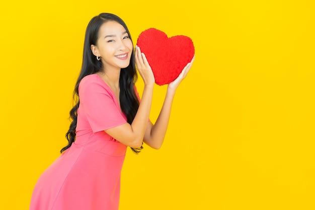 Glimlachen van de portret de mooie jonge aziatische vrouw met de vorm van het harthoofdkussen op gele muur