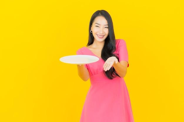 Glimlachen van de portret de mooie jonge aziatische vrouw met lege plaatschotel op gele muur