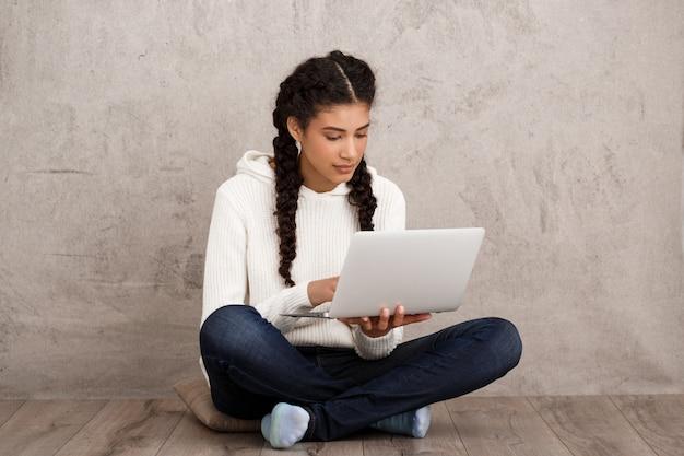 Glimlachen van het meisje, die laptop houdt, die op vloer over beige muur zit