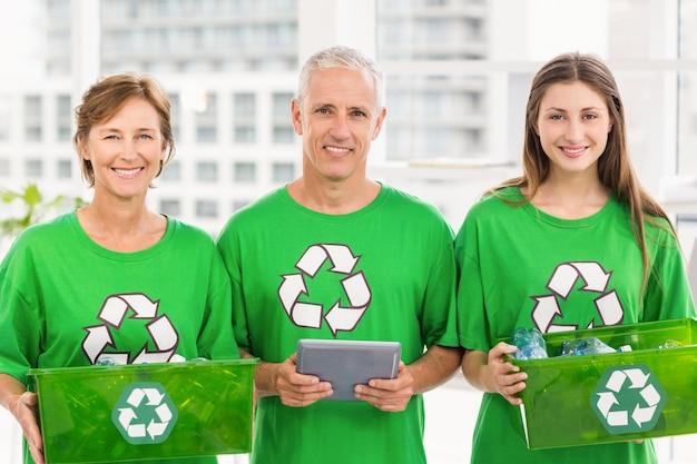 Glimlachen van milieubewuste collega's met recyclingsdozen
