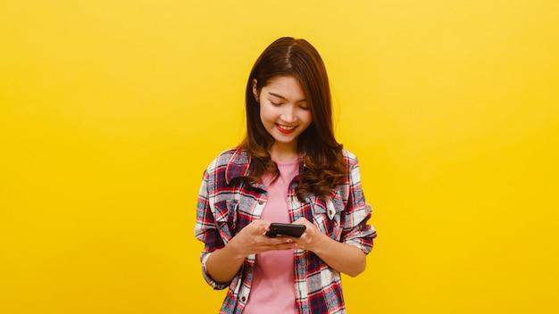 Glimlachend aanbiddelijk aziatisch wijfje die telefoon met positieve uitdrukking gebruiken, breed glimlachen, gekleed in vrijetijdskleding en camera over gele muur bekijken. de gelukkige aanbiddelijke blije vrouw verheugt zich succes.