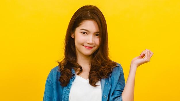 Glimlachend aanbiddelijk aziatisch wijfje met positieve uitdrukking, brede glimlach, gekleed in vrijetijdskleding en bekijkend de camera over gele muur. de gelukkige aanbiddelijke blije vrouw verheugt zich succes.