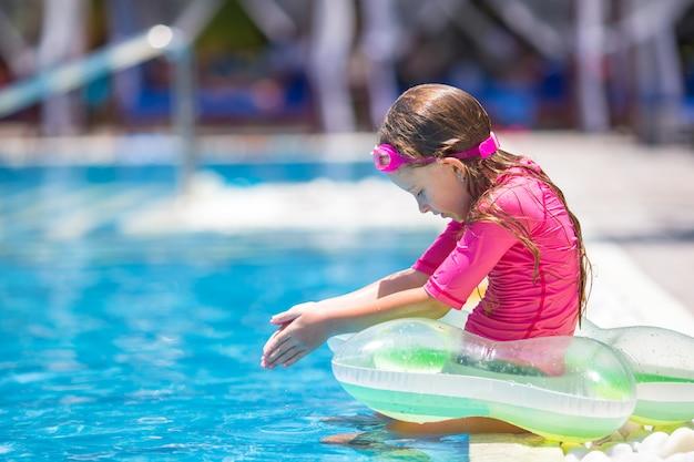 Glimlachend aanbiddelijk meisje dat pret in openlucht zwembad heeft