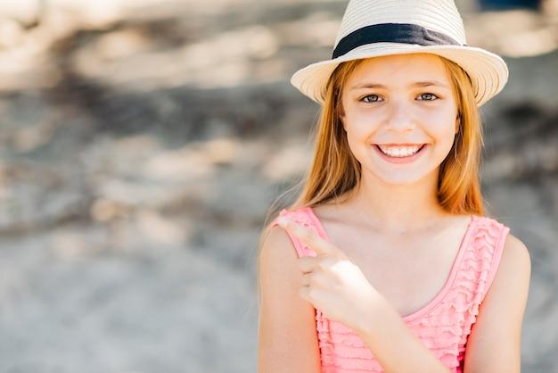 Glimlachend aanbiddelijk meisje die met vinger richten die camera in daglicht bekijken