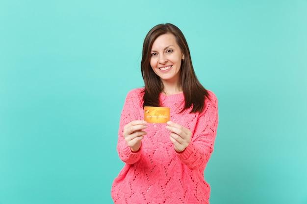 Glimlachend aantrekkelijk jong meisje in gebreide roze trui op zoek naar camera, creditcard in de hand houden geïsoleerd op blauwe turquoise muur achtergrond studio portret. mensen levensstijl concept. bespotten kopie ruimte.