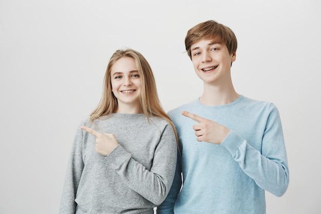 Glimlachend aantrekkelijk meisje en kerel die vingers verlaten bij banner