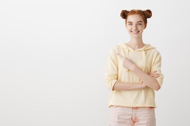 Glimlachend aantrekkelijk meisje met rood haar wijzende vinger naar links