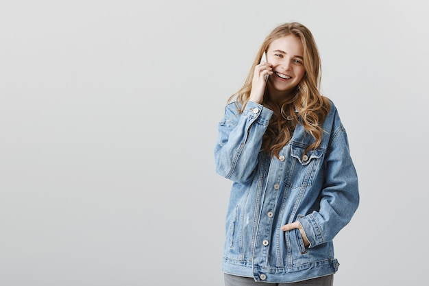 Glimlachend aantrekkelijk meisje praten over telefoon met blij gezicht