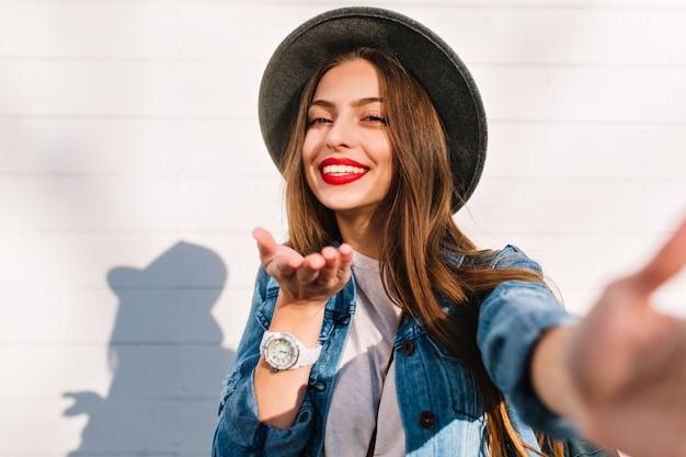 Glimlachend aantrekkelijk modieus meisje die grijze hoed en wit polshorloge dragen die pret met camera hebben en luchtkus verzenden.