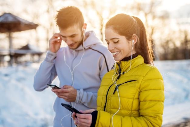 Glimlachend actief paar met oortelefoons in de wintersportkleding die muziekafspeellijst voorbereiden alvorens naar buiten te rennen in sneeuwnatuur.