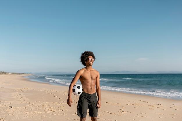 Glimlachend afrikaans amerikaans mannetje dat zich met bal op kust bevindt