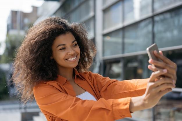 Glimlachend afrikaans amerikaans meisje dat het selfies mobiel gebruiken neemt