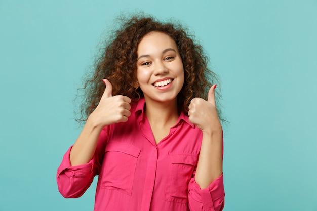 Glimlachend afrikaans amerikaans meisje in casual kleding duimen opdagen, op zoek naar camera geïsoleerd op blauwe turquoise muur achtergrond in studio. mensen oprechte emoties, lifestyle concept. bespotten kopie ruimte.