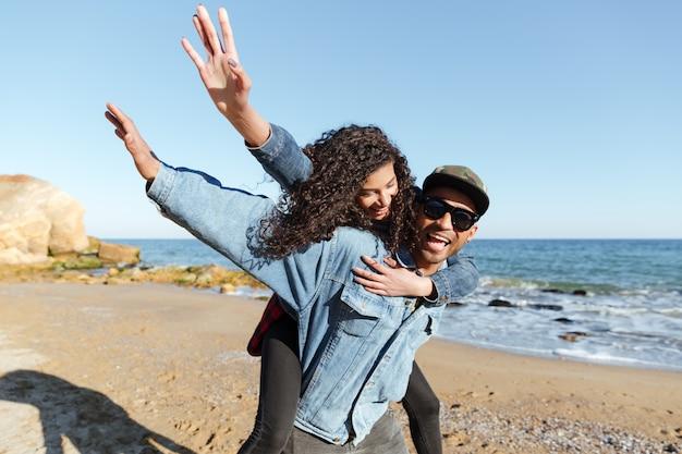 Glimlachend afrikaans houdend van paar dat in openlucht bij strand loopt