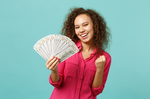 Glimlachend afrikaans meisje dat winnaargebaar doet, houdt fan van geld in dollarbankbiljetten, contant geld geïsoleerd op blauwe turquoise muurachtergrond. mensen oprechte emoties, lifestyle concept. bespotten kopie ruimte.
