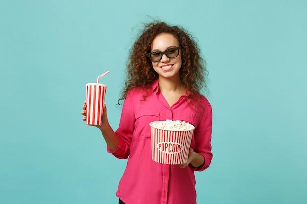 Glimlachend afrikaans meisje in 3d imax bril kijken naar film film houd popcorn, kopje frisdrank geïsoleerd op blauwe turkooizen achtergrond in studio. mensen emoties in de bioscoop, lifestyle concept. bespotten kopie ruimte.