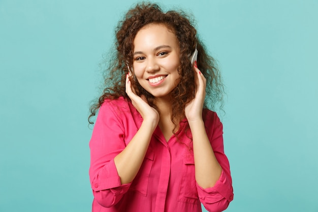 Glimlachend afrikaans meisje in casual kleding op zoek naar camera, muziek luisteren met koptelefoon geïsoleerd op blauwe turkooizen achtergrond in studio. mensen oprechte emoties, lifestyle concept. bespotten kopie ruimte.