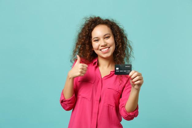 Glimlachend afrikaans meisje in roze casual kleding met duim omhoog houd creditcard geïsoleerd op blauwe turquoise muur achtergrond in studio. mensen oprechte emoties, lifestyle concept. bespotten kopie ruimte.