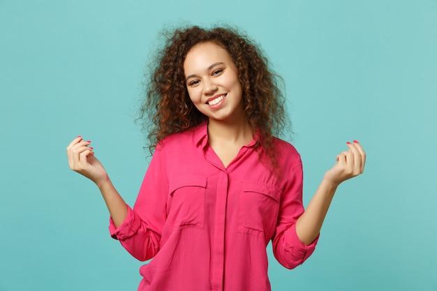 Glimlachend afrikaans meisje in roze vrijetijdskleding wrijven vingers, contant gebaar tonen, vragen om geld geïsoleerd op blauwe turquoise muur achtergrond in studio. mensen oprechte emoties levensstijl concept. moc