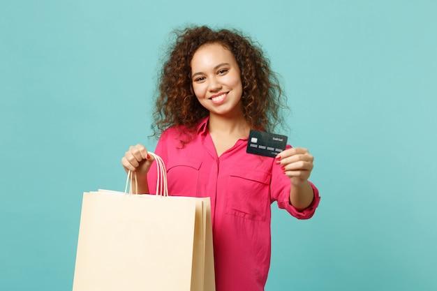 Glimlachend afrikaans meisje in vrijetijdskleding houdt pakkettas met aankopen vast na het winkelen, creditcard geïsoleerd op blauwe turkooizen achtergrond. mensen oprechte emoties levensstijl concept. bespotten kopie ruimte.