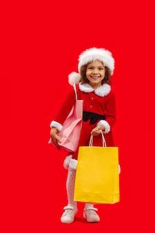 Glimlachend afro-amerikaanse babymeisje in rode kleren en rode kerstmuts met boodschappentassen in haar hand op rood