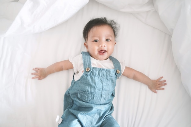 Glimlachend aziatisch babymeisje dat op een bed ligt.