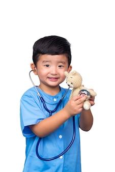 Glimlachend aziatisch jong geitje in blauwe medische eenvormige die holdingsstethoscoop op wit met het knippen van weg wordt geïsoleerd.