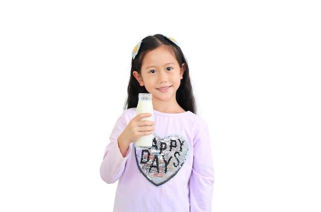 Glimlachend aziatisch jong geitjemeisje met de fles van het melkglas dat op witte muur wordt geïsoleerd