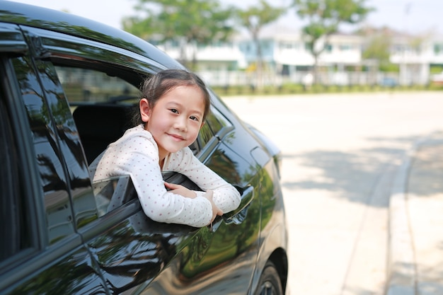 Glimlachend aziatisch klein kindmeisje dat in de auto zit en naar de camera kijkt, komt uit het autoraam