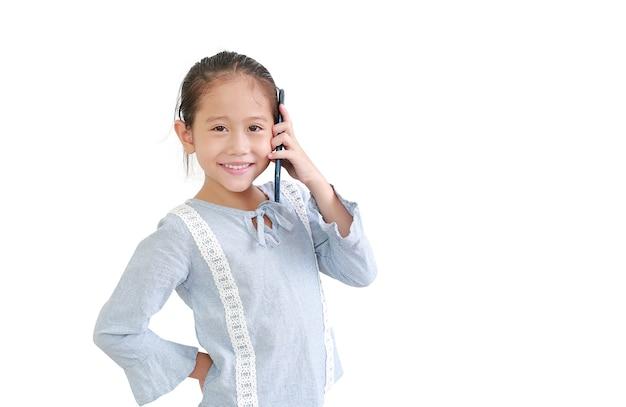 Glimlachend aziatisch klein kindmeisje die smartphone gebruiken die op witte achtergrond wordt geïsoleerd
