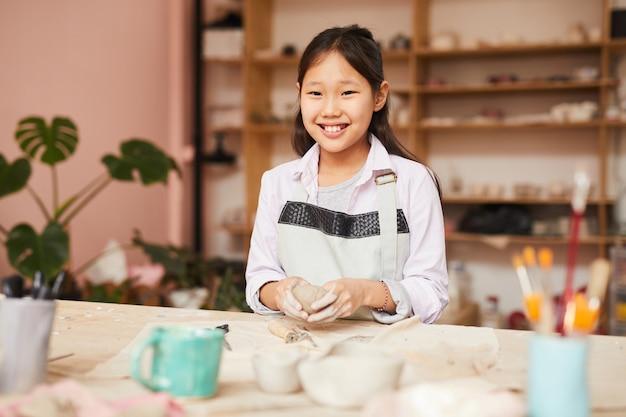 Glimlachend aziatisch meisje dat aardewerk van klasse geniet