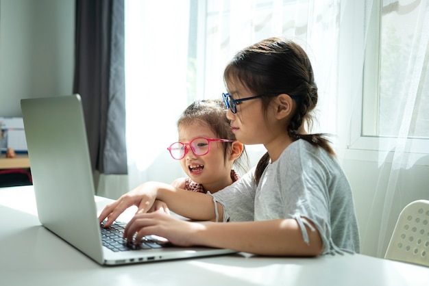 Glimlachend aziatisch meisje en zus met laptopcomputer voor homeschooling studie, online onderwijs thuis samen. sociale afstand, thuisonderwijs of online leerconcept