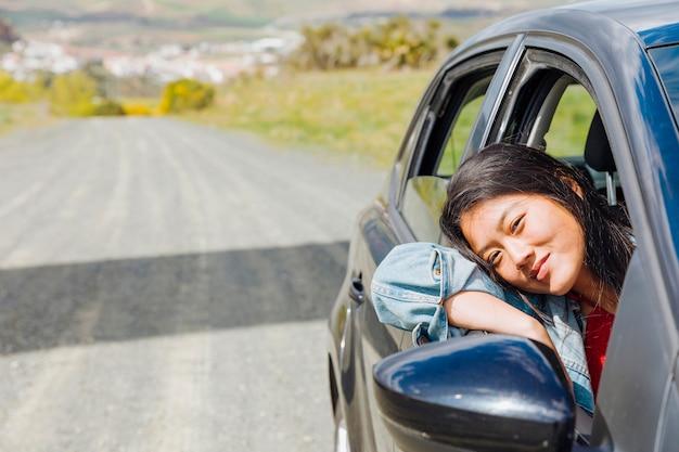 Glimlachend aziatisch wijfje dat uit auto kijkt