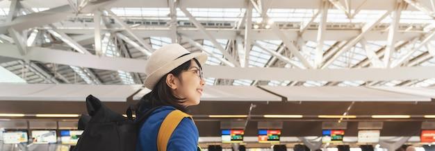 Glimlachend aziatisch wijfje die dichtbij incheckbalie wachten in de terminal van het luchthavenvertrek.