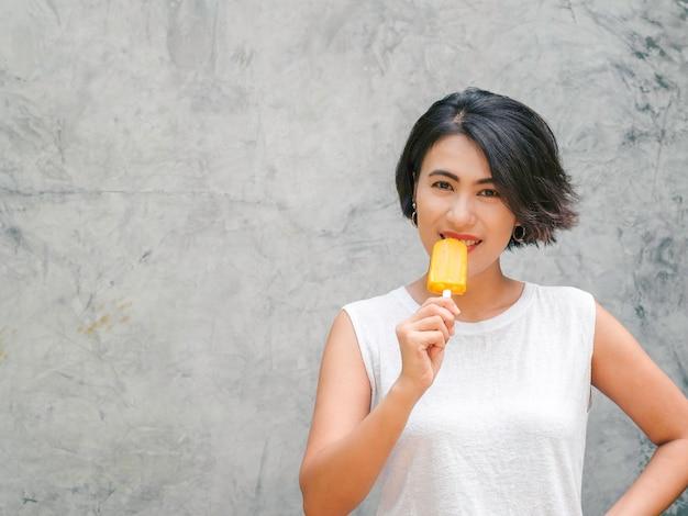 Glimlachend aziatische vrouw kort haar in casual wit mouwloos shirt gele ijslolly eten op grijze betonnen muur achtergrond in de zomer. vrouwen die ijslolly's met exemplaarruimte eten.